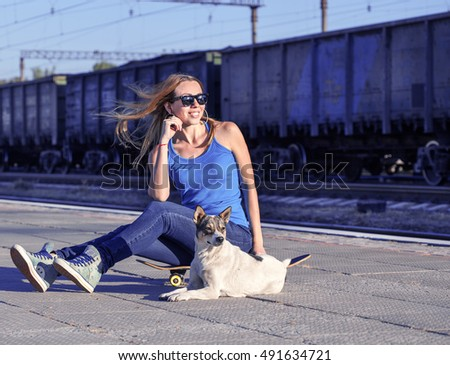 Portrait of attractive girl with a skateboard. Woman and dog on railway station