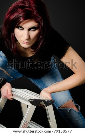 Portrait of attractive, girl with attitude leaning on a step-ladder - stock photo