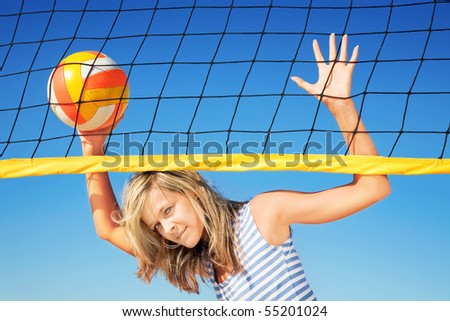 Portrait of attractive girl with ball near volleyball net - stock photo
