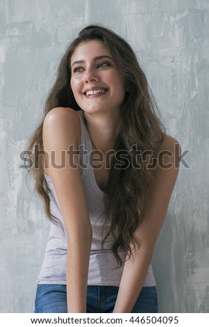 Portrait of attractive happy model with long brunette hair looking away with smile.Textured wall on background - stock photo