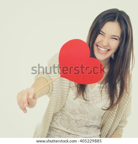 portrait of attractive happy smiling teen girl with red heart, love holiday valentine symbol. Image toned and noise added.