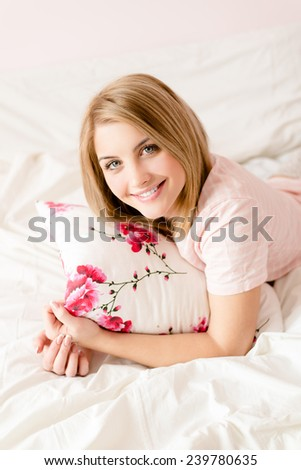 portrait of attractive happy young blond woman in bed with floral pillow in hand  & looking at camera - stock photo
