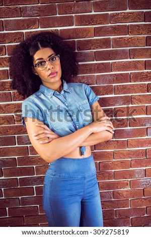 Portrait of attractive hipster with arms crossed leaning against red brick background - stock photo