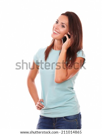 Portrait of attractive hispanic woman on blue t-shirt speaking on her cell while standing and smiling on isolated studio - stock photo