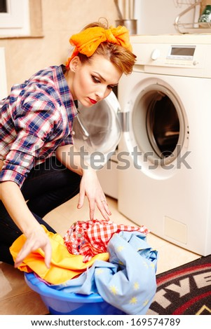 Portrait of attractive housewife putting the laundry into the washing machine - stock photo