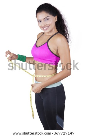 Portrait of attractive indian woman taking body measurements, isolated on white background - stock photo