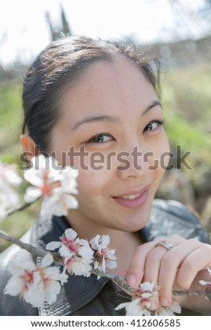Portrait of attractive Korean girl in blossoming park. Asian girl looks at camera through blossoming almond branches - stock photo