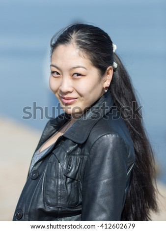Portrait of attractive Korean girl outdoors. Asian girl looking at camera smiling - stock photo
