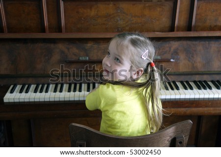 Portrait of attractive little girl, playing on piano - stock photo