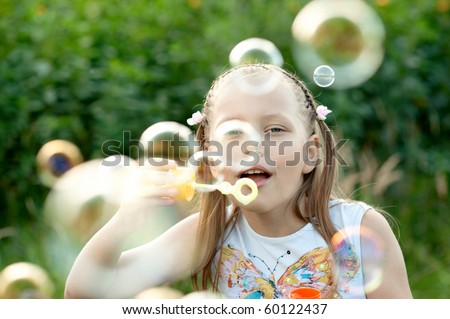 Portrait of attractive little girl with soap bubbles