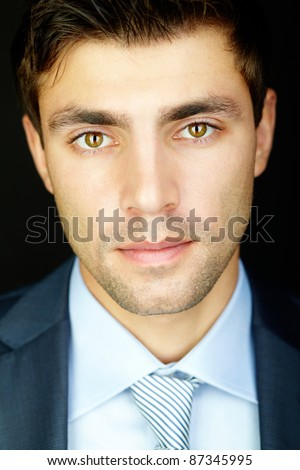 Portrait of attractive male looking at camera in darkness - stock photo
