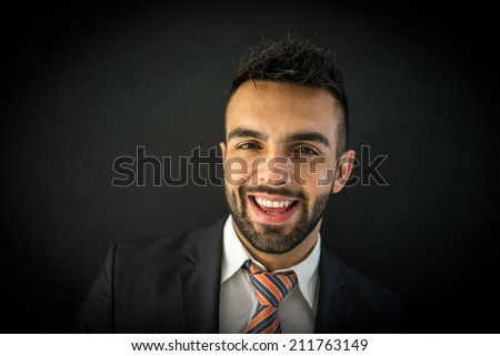Portrait of attractive man against black background smiling - stock photo