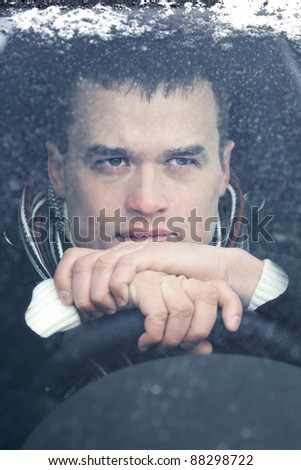 Portrait of attractive man in car in winter time - stock photo