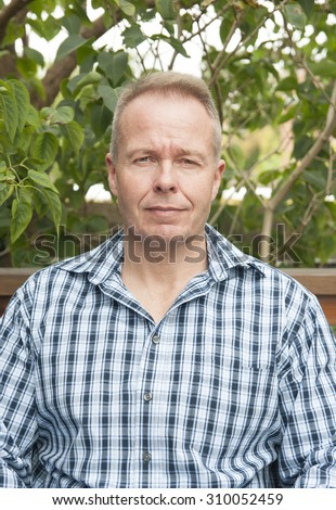 Portrait of attractive man in the garden - stock photo