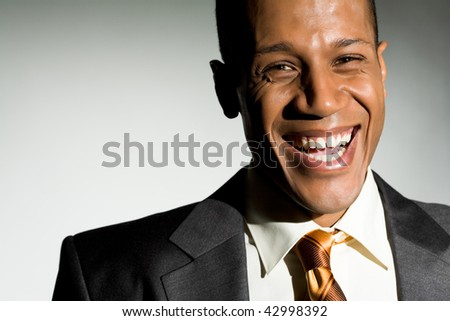 Portrait of attractive man looking at camera and laughing - stock photo