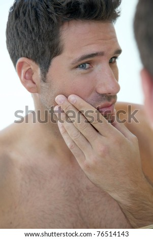 Portrait of attractive man looking at mirror