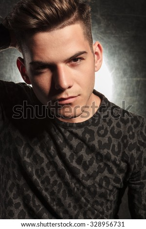 portrait of attractive man posing while fixing his stylish hair