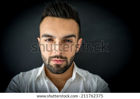 Portrait of attractive man standing on black wall