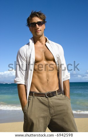 Portrait of attractive man standing with shirt unbuttoned wearing sunglasses on Maui, Hawaii beach. - stock photo
