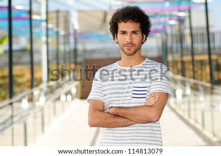 Portrait of attractive man with curly hairstyle in urban background - stock photo