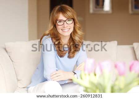 Portrait of attractive mature woman sitting at sofa and relaxing at home.  - stock photo