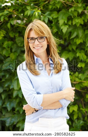 Portrait of attractive middle age woman looking at camera and smiling while standing in garden.  - stock photo
