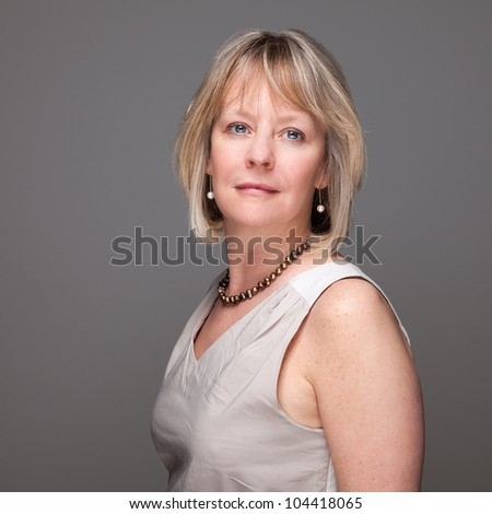 Portrait of Attractive Middle Age Woman with Enigmatic Look on Grey Background - stock photo