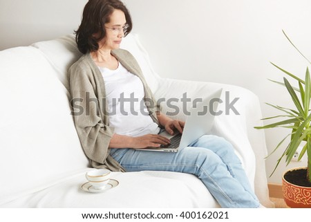 Portrait of attractive middle-aged brunette businesswoman in eyeglasses at home working on laptop computer while work at office work. Content woman sitting on her couch using laptop smiling in room - stock photo