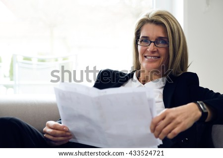 Portrait of attractive middle-aged business woman sitting on modern sofa at home and smiling into the camera. Confident woman with black suit reading white papers in bright environment. - stock photo