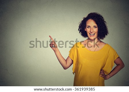 Portrait of attractive middle aged woman pointing at blank gray wall background - stock photo