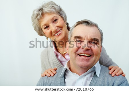 Portrait of attractive middle woman embracing her husband over white background