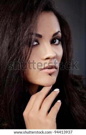 Portrait of attractive mixed race woman with hand on chin on a black background