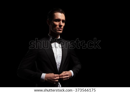 portrait of attractive model in black tux with bowtie posing looking away while closing jacket in dark studio background - stock photo