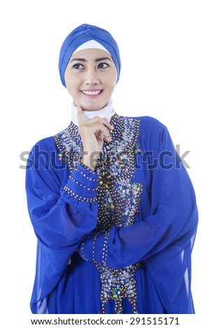 Portrait of attractive muslim woman wearing islamic clothes. Smiling and thinking something while looking up, shot in the studio - stock photo