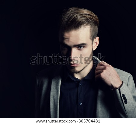 Portrait of attractive mysterious young man over black background. - stock photo