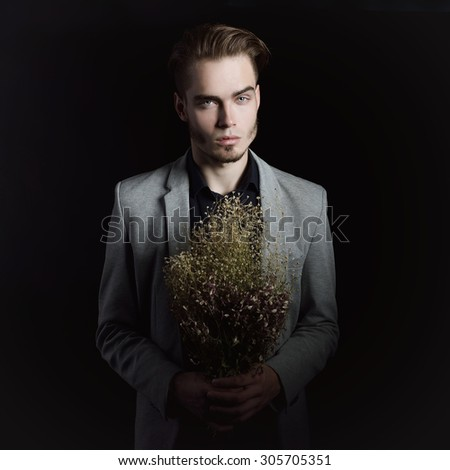 Portrait of attractive mysterious young man with dry flowers over black background. - stock photo