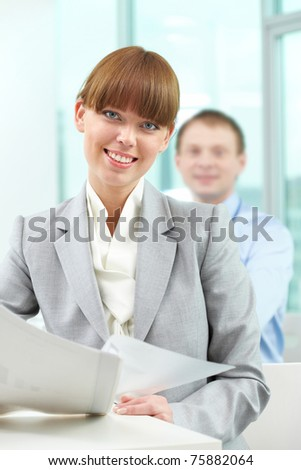 Portrait of attractive office worker looking at camera with man on background