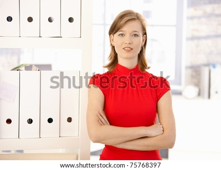 Portrait of attractive office worker, wearing red shirt. Looking at camera, smiling. - stock photo