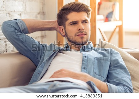 Portrait of attractive pensive young man looking away and thinking while lying on sofa at home - stock photo