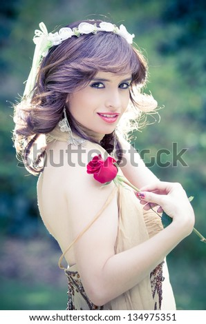 portrait of attractive pricess  outdoors witha rose - stock photo