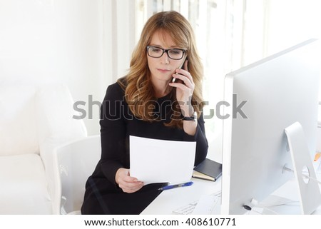 Portrait of attractive professional manager woman making call while analyzing financial data.