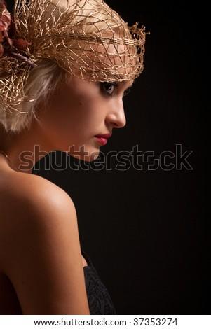 Portrait of attractive retro-style girl in bonnet over black - stock photo