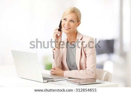 Portrait of attractive sales woman making call while sitting at office in front of laptop and working.  - stock photo