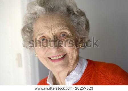Portrait of attractive senior woman standing by front door - stock photo