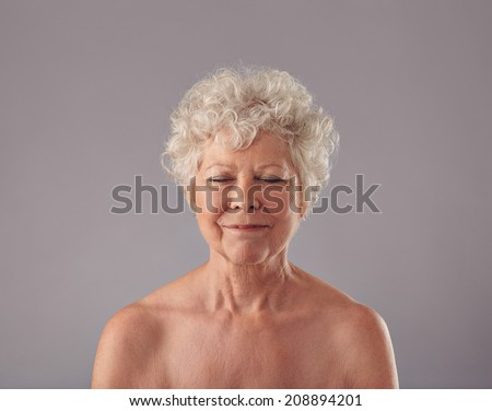 Portrait of attractive senior woman with her eyes closed in thought against grey background.  - stock photo