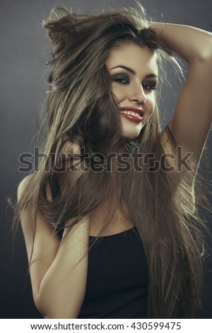 Portrait of attractive sensual flirtatious young woman playing with her hands through her brown long silky hair with fluttering strands. Hair health, hair freshness, hair care. - stock photo