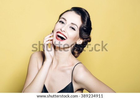 Portrait of attractive sensual glamour retro elegant young adult smiling woman with classic hairstyle and red lips in silk night dress indoor on yellow background, horizontal picture - stock photo