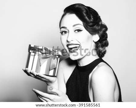 Portrait of attractive sensual glamour retro elegant young adult smiling woman with classic hairstyle and red lips in evening dress holding present box indoor black and white, horizontal picture - stock photo
