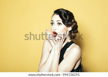 Portrait of attractive sensual glamour retro elegant young adult surprised woman with classic hairstyle and red lips in evening dress indoor on yellow background, horizontal picture - stock photo