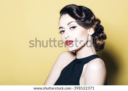Portrait of attractive sensual glamour retro elegant young adult thoughtful woman with classic hairstyle and red lips in evening dress indoor on yellow background, horizontal picture - stock photo